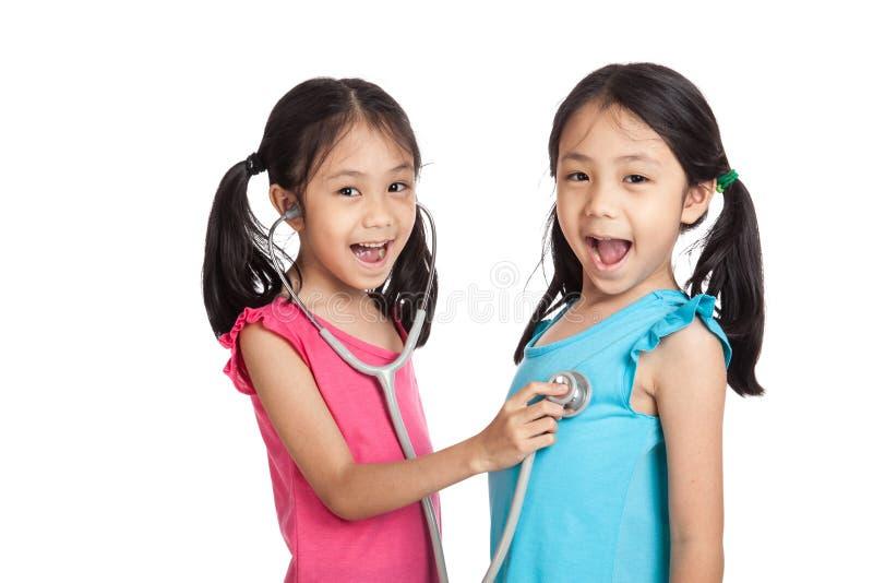 Szczęśliwe Azjatyckie bliźniak dziewczyny z stetoskopem obraz stock