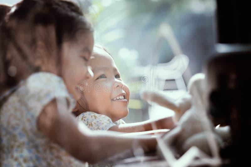 Szczęśliwe azjatykcie małe dziewczynki ono uśmiecha się wpólnie i bawić się w kawiarni zdjęcie stock