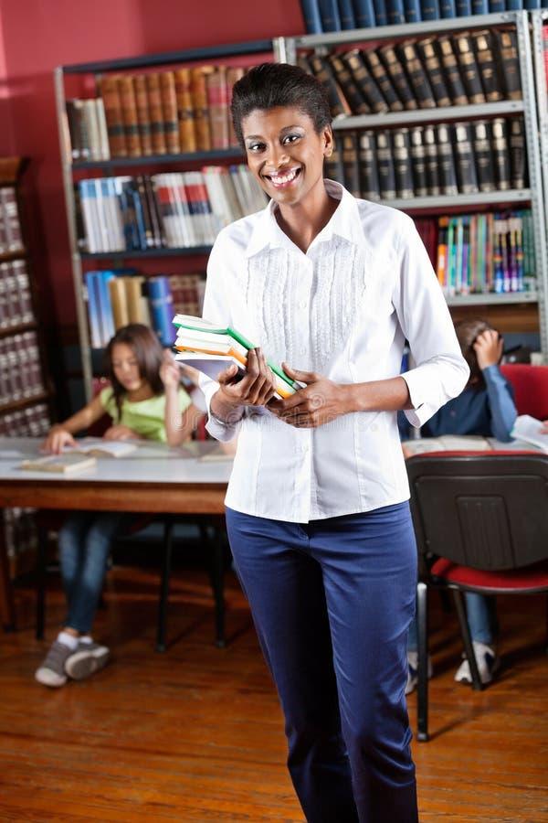 Szczęśliwe Bibliotekarskie mienie książki Podczas gdy Stojący Wewnątrz zdjęcie stock