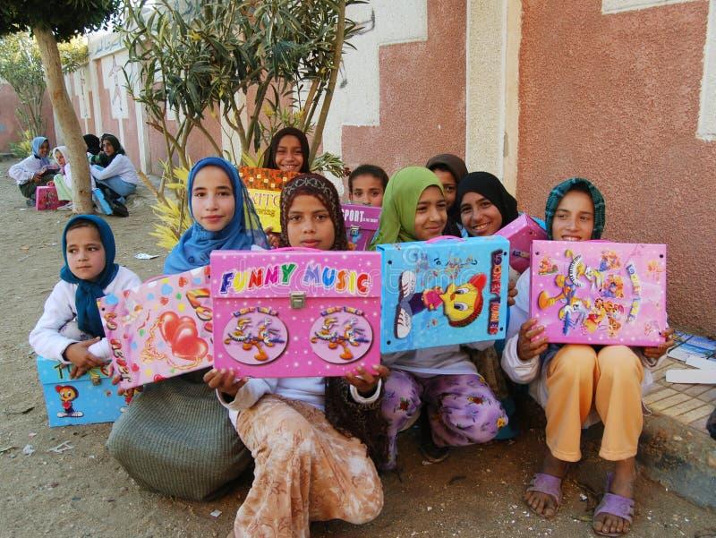 Szczęśliwe biedne muzułmańskie dziewczyny w przesłonie otrzymywali teraźniejszość i prezenty w Egipt obraz stock