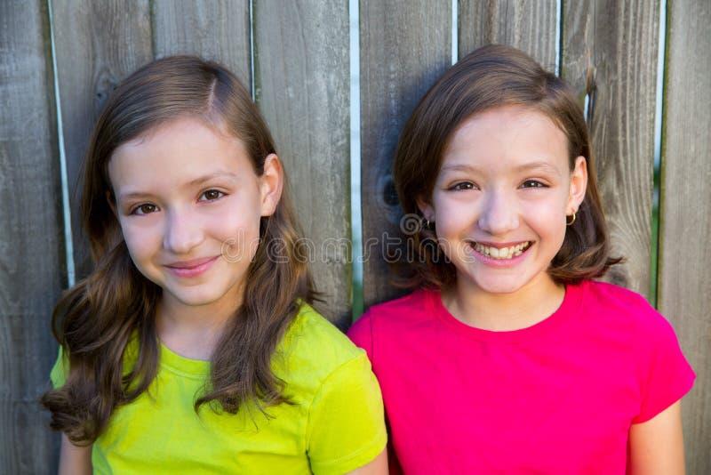Szczęśliwe bliźniacze siostry ono uśmiecha się na drewnianym podwórku one fechtują się obrazy stock