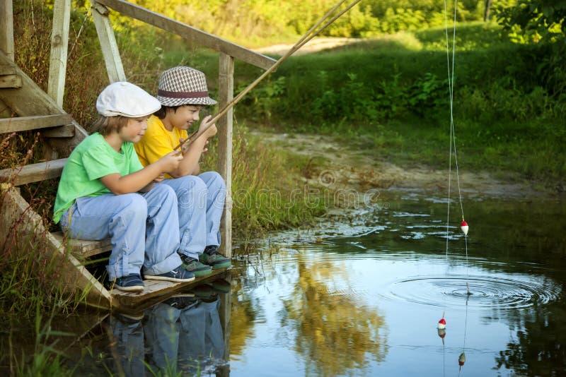 Szczęśliwe chłopiec iść łowić na rzece, Dwa dziecka fisherma obrazy royalty free