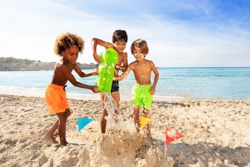 Szczęśliwe chłopiec robi sandcastle wpólnie na plaży fotografia royalty free