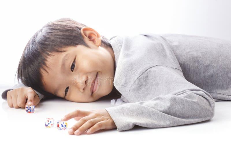 Szczęśliwe chłopiec sztuki dices na stole zdjęcia royalty free