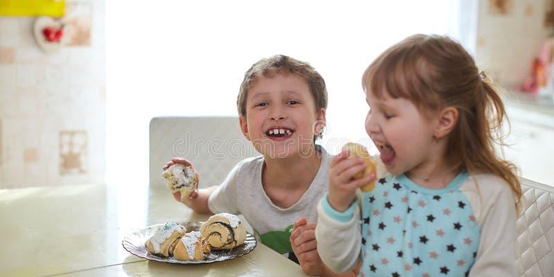 szczęśliwe dzieci jedzą ciastka w jasnej kuchni zdjęcia stock
