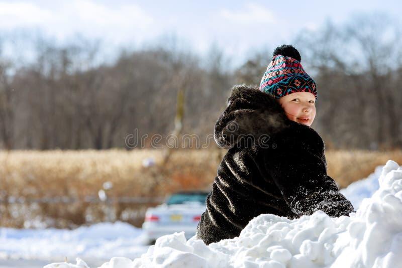 Szczęśliwe dziecko bawiące się śniegiem w zimowy dzień obraz stock