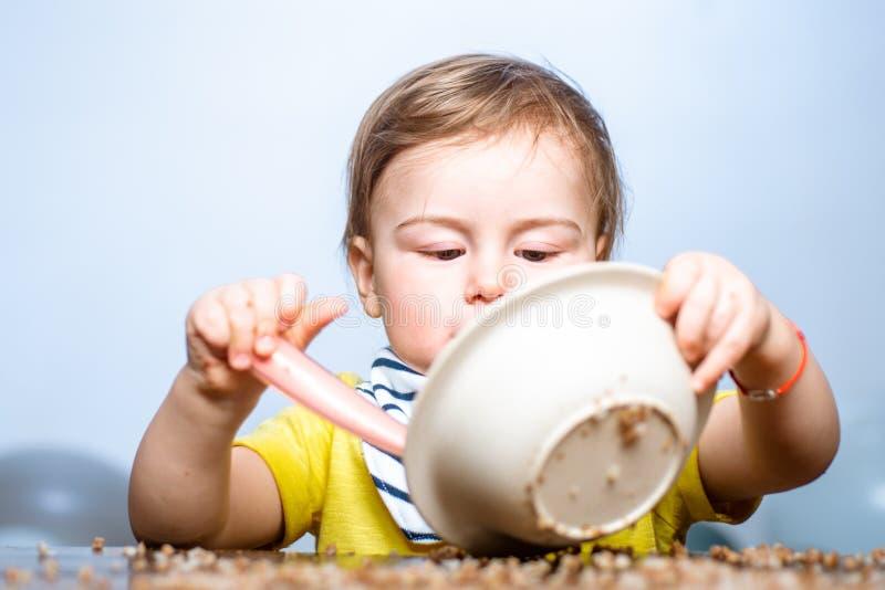 Szczęśliwe dziecko z łyżką Jedzenie dziecka Dzieciak gra w kuchni z daniami Szczęśliwy chłopczyk łyżeczka zjada się zdjęcia royalty free