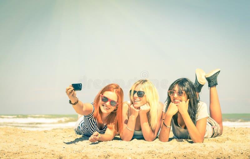 Szczęśliwe dziewczyny bierze lata selfie przy plażą fotografia stock