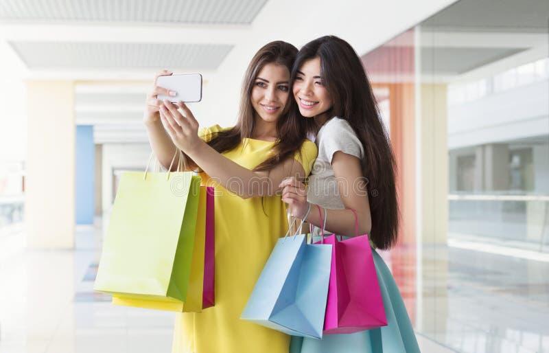 Szczęśliwe dziewczyny bierze selfie podczas gdy robiący zakupy w centrum handlowym obraz stock
