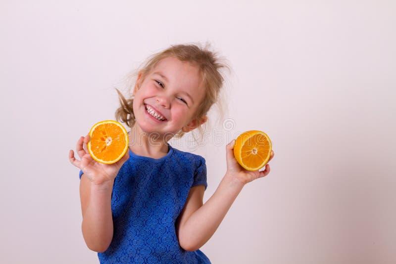 Szczęśliwe dziewczyny mienia połówki pomarańcze zdjęcia stock