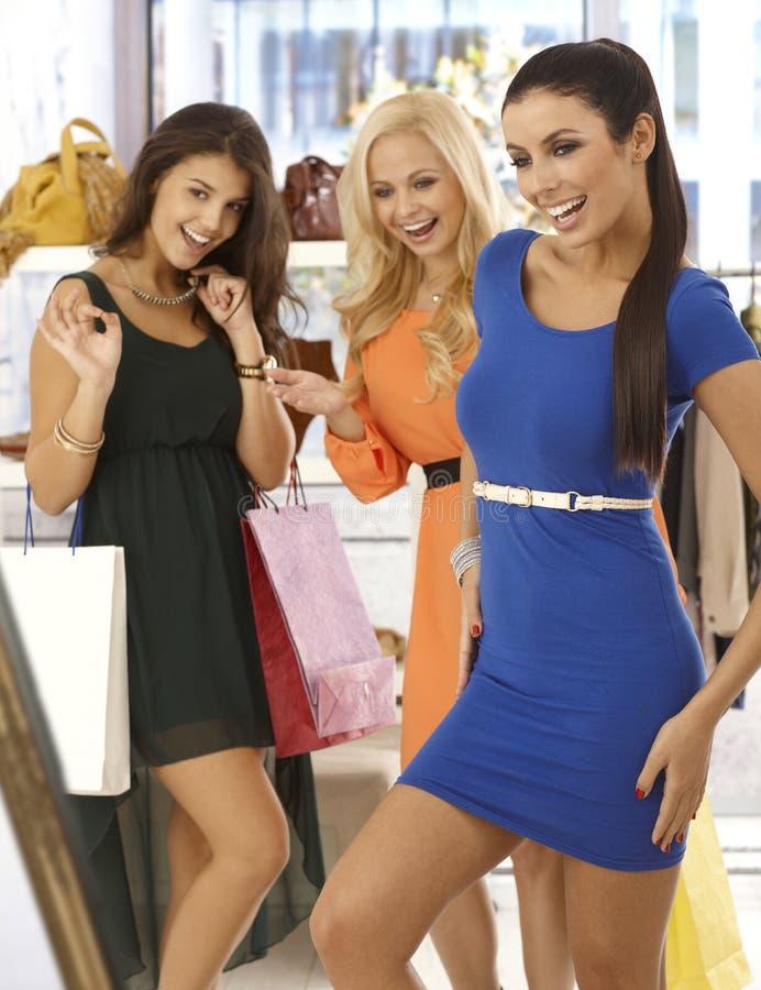 Szczęśliwe dziewczyny przy ubrania sklepem obraz stock