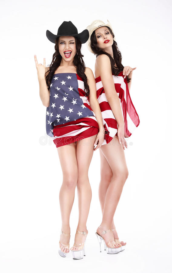 Szczęśliwe dziewczyny w kapeluszy i flaga amerykańskiej pozować zdjęcia stock