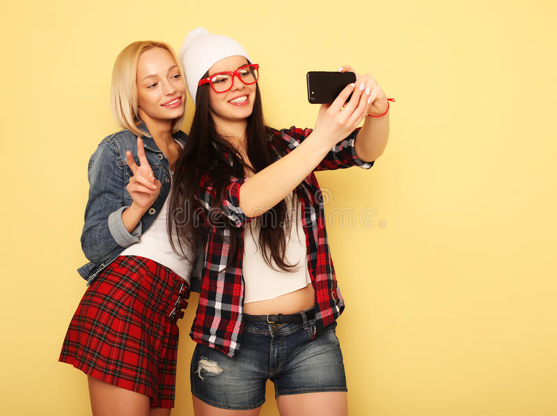 Szczęśliwe dziewczyny z smartphone nad żółtym tłem Szczęśliwa jaźń zdjęcie stock