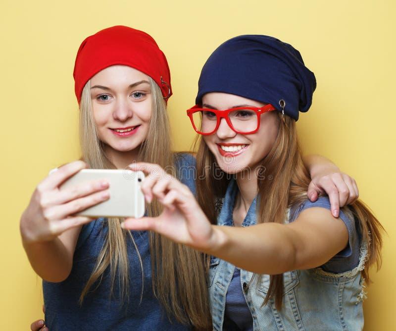Szczęśliwe dziewczyny z smartphone nad żółtym tłem Szczęśliwa jaźń zdjęcia royalty free
