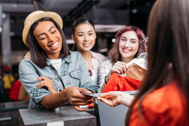 Szczęśliwe eleganckie młode kobiety płaci z kredytową kartą w zakupy centrum handlowym fotografia stock