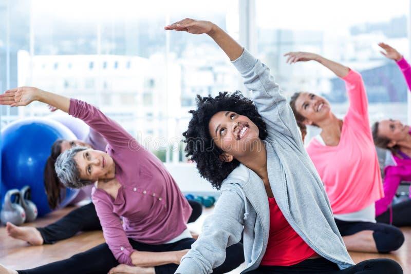 Szczęśliwe kobiety ćwiczy podczas gdy ręki podnosili zdjęcia stock