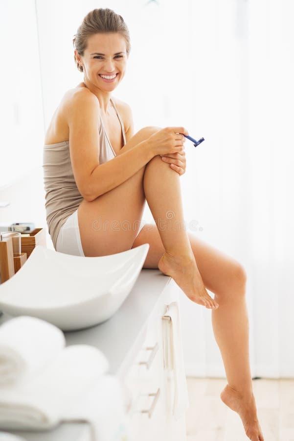 Szczęśliwe kobiety golenia nogi w łazience zdjęcia stock