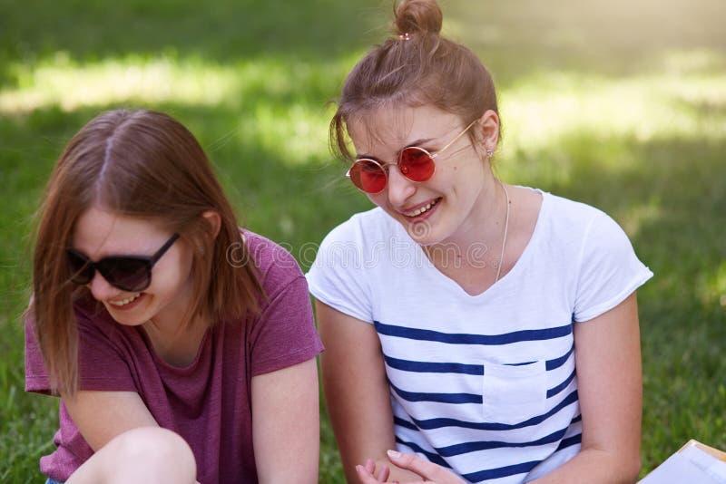 Szczęśliwe kobiety opowiada i śmia się w parku, siedzi na trawie, odzieży przypadkowi ubrania i okulary przeciwsłoneczni, słuchaj zdjęcia royalty free