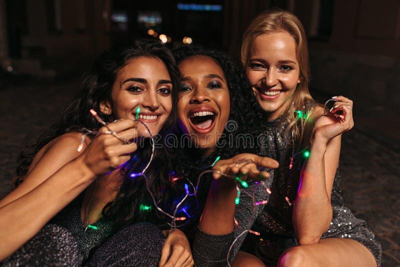 Szczęśliwe kobiety trzyma bożonarodzeniowe światła w rękach zdjęcia stock