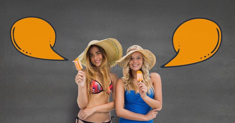 Szczęśliwe kobiety z mową gulgoczą łasowanie lody przeciw popielatemu tłu fotografia stock