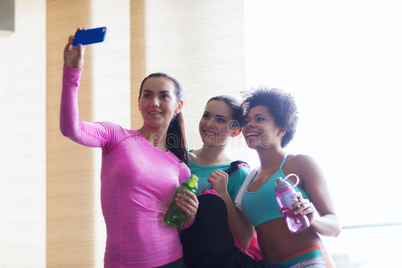 Szczęśliwe kobiety z smartphone bierze selfie w gym zdjęcia royalty free