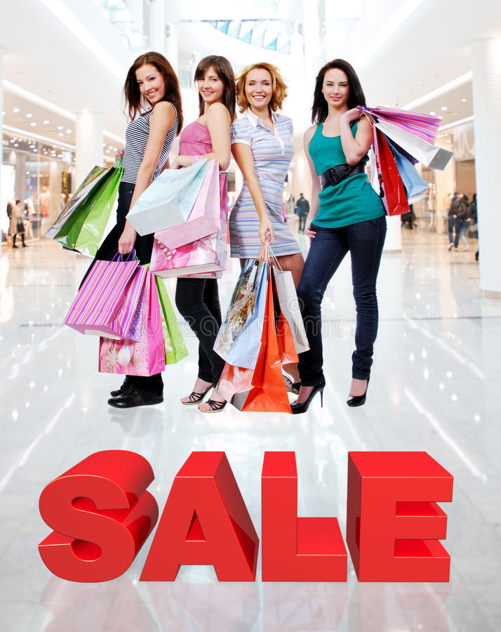 Szczęśliwe kobiety z torba na zakupy przy sklepem zdjęcie stock