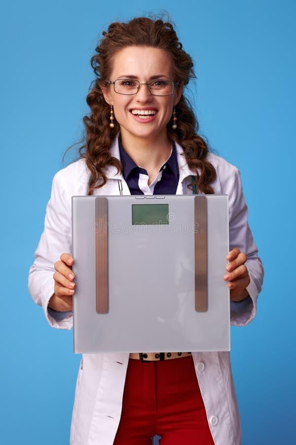 Szczęśliwe lekarz kobiety seansu skale na błękicie obrazy stock