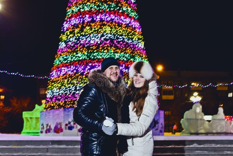 Szczęśliwe mężczyzny i kobiety mienia ręki na choinki tle obraz royalty free