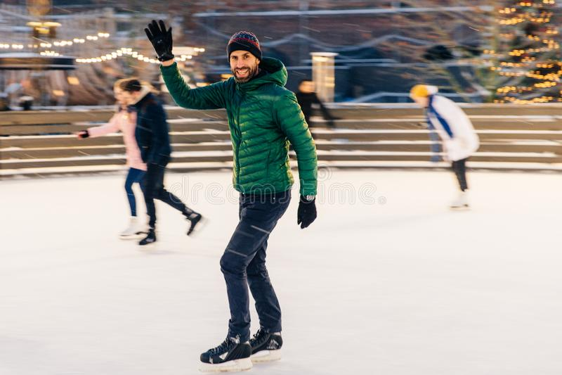 Szczęśliwe męskie fala z ręką jak zauważa jego przyjaciel na łyżwiarstwo pierścionku zdjęcie royalty free