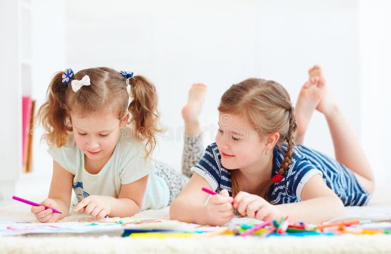 Szczęśliwe młode dziewczyny, dzieciaki maluje z odczuwanym piórem wpólnie fotografia stock