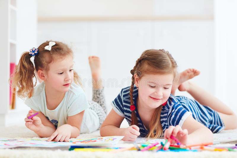 Szczęśliwe młode dziewczyny, dzieciaki maluje z odczuwanym piórem wpólnie obrazy royalty free