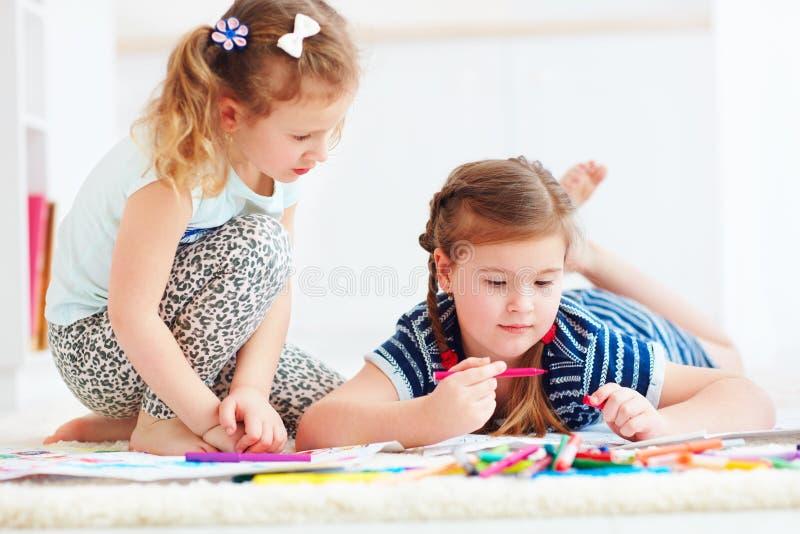 Szczęśliwe młode dziewczyny, dzieciaki maluje z odczuwanym piórem wpólnie obraz stock
