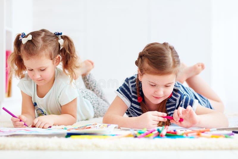 Szczęśliwe młode dziewczyny, dzieciaki maluje z odczuwanym piórem wpólnie obrazy stock