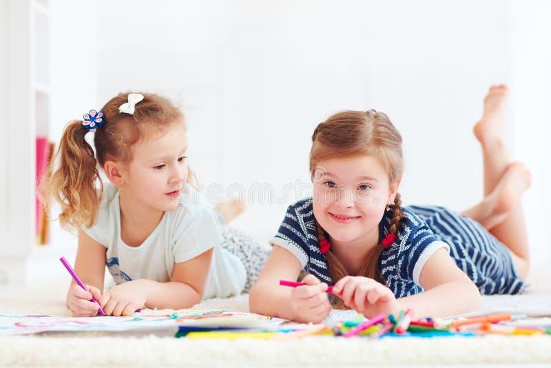 Szczęśliwe młode dziewczyny, dzieciaki maluje z odczuwanym piórem wpólnie obraz royalty free