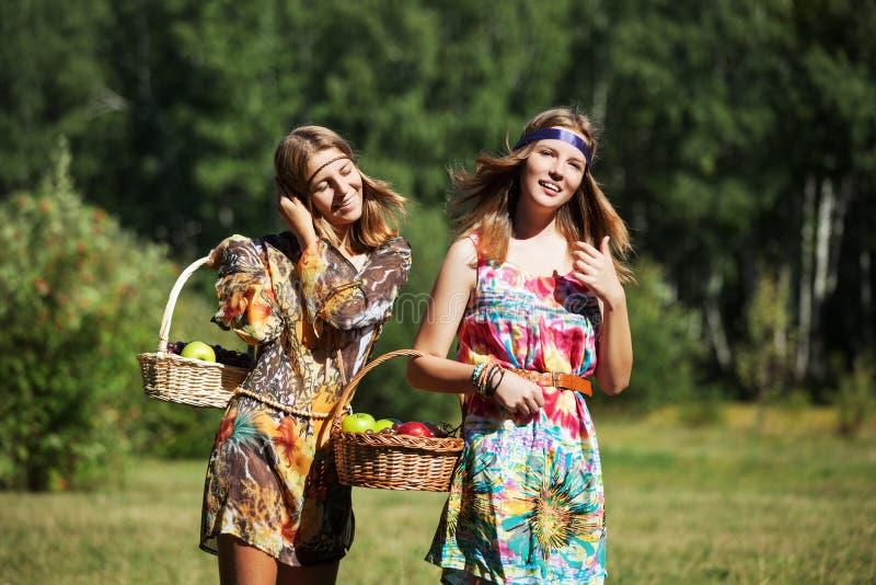 Szczęśliwe młode dziewczyny z owocowym koszem na naturze fotografia royalty free