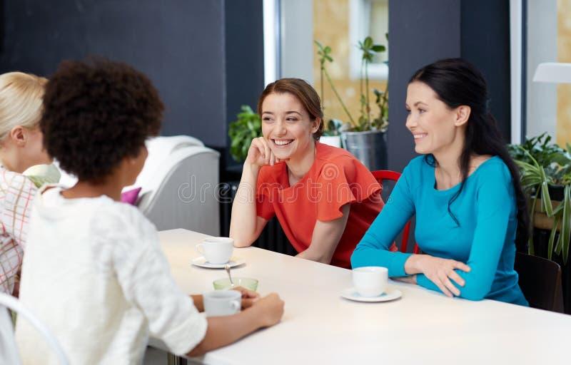 Szczęśliwe młode kobiety pije herbaty lub kawy przy kawiarnią fotografia royalty free