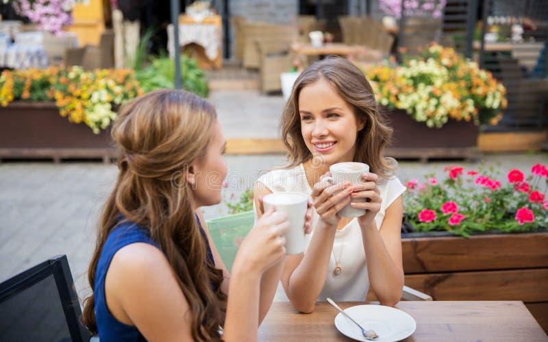 Szczęśliwe młode kobiety pije kawę przy plenerową kawiarnią zdjęcia royalty free