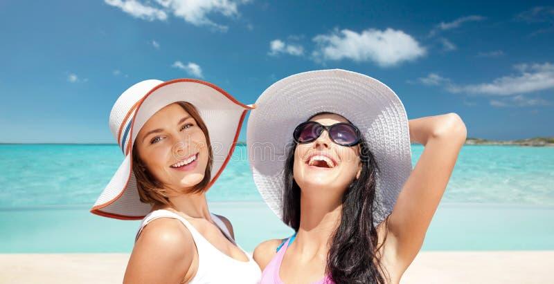 Szczęśliwe młode kobiety w kapeluszach na lato plaży obraz royalty free