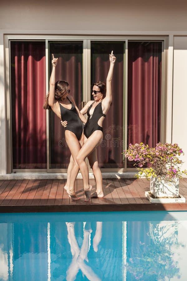 szczęśliwe młode kobiety w swimsuits tanczyć zdjęcia stock