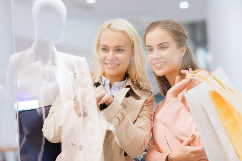 Szczęśliwe młode kobiety z torba na zakupy w centrum handlowym obrazy royalty free