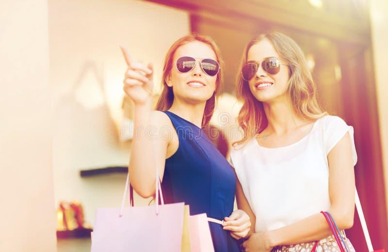 Szczęśliwe młode kobiety z torba na zakupy w centrum handlowym obraz royalty free