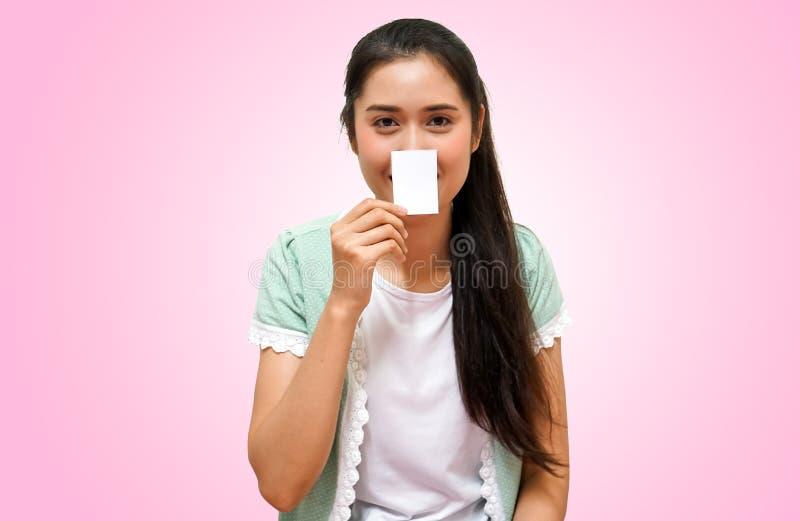 Szczęśliwe młode piękne kobiety w t-sirt przedstawienia prawa ręka papierze dla teksta projektują pozycję odizolowywając fotografia royalty free