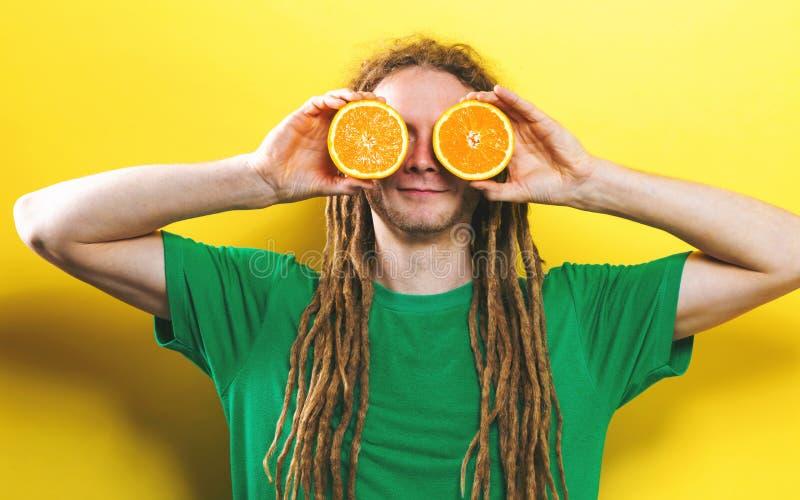 Szczęśliwe młodego człowieka mienia pomarańcze obraz stock