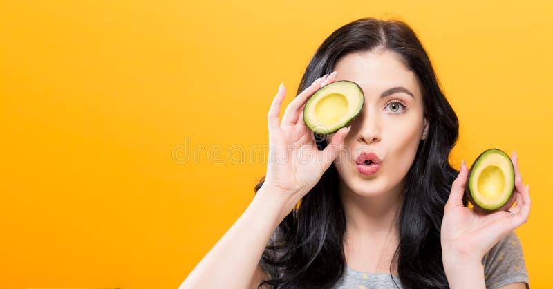 Szczęśliwe młodej kobiety mienia avocado połówki zdjęcie royalty free
