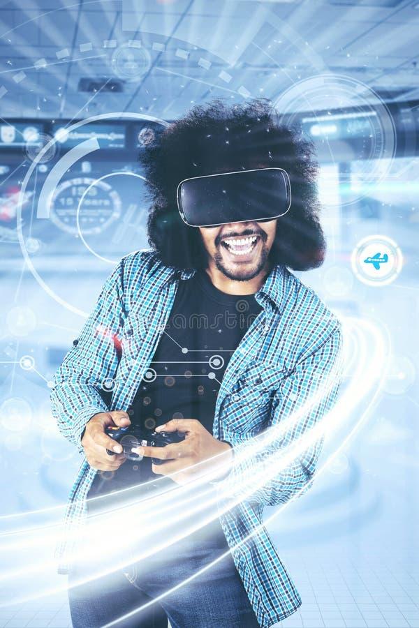 Szczęśliwe młody człowiek sztuki gry z futurystycznym ekranem obrazy stock