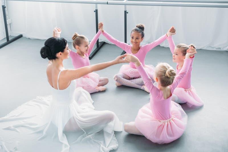 szczęśliwe małe baleriny i baletnicze ręki nauczyciela mienia i obsiadania obraz royalty free