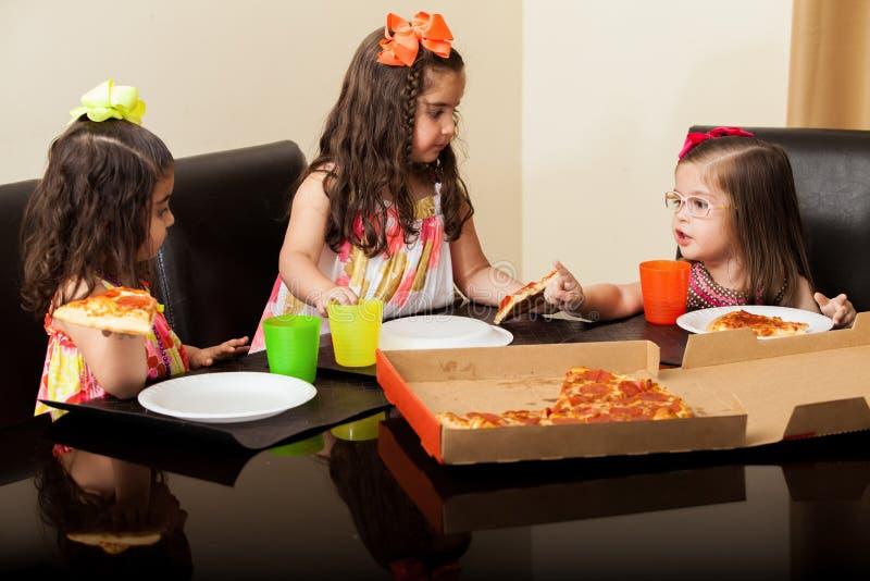Szczęśliwe małe dziewczynki ma niektóre pizzę obrazy stock