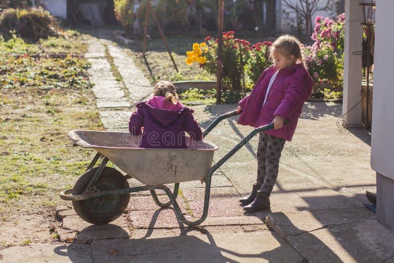 Szczęśliwe małe dziewczynki z wheelbarrow zdjęcie royalty free