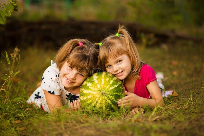 Szczęśliwe małe siostry kłamają na trawie i ściskają bardzo dużego arbuza w słonecznym dniu pojęcie zdrowy zdjęcie stock