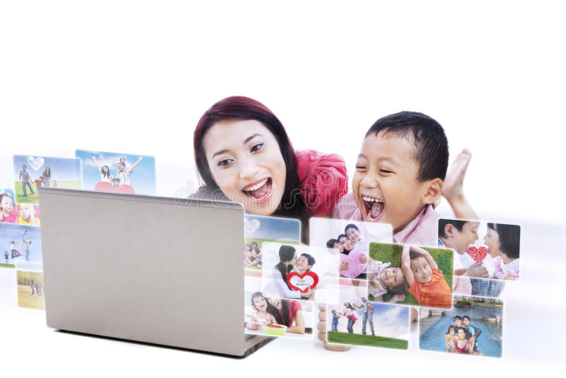 Szczęśliwe macierzyste patrzeje cyfrowe rodzinne fotografie - odosobnione